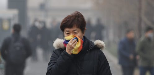 A woman covers her mouth with her scarf as she walks in smog.