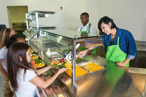 Two cafeteria workers serve food to children during lunch.