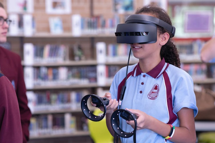 Person wearing extended reality headset in a library.