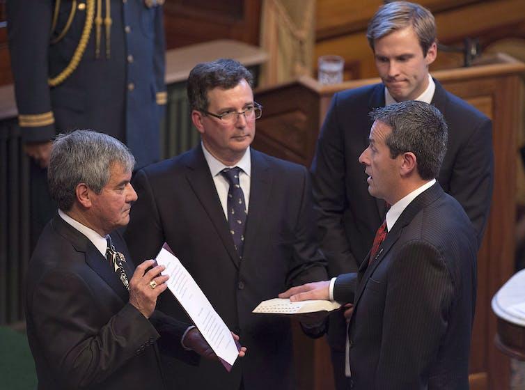 Un homme prête serment en compagnie de trois dignitaires
