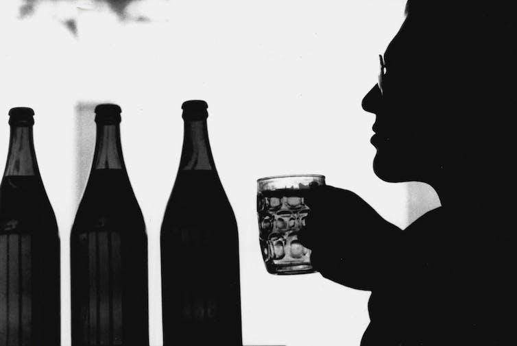 man holding glass next to bottles