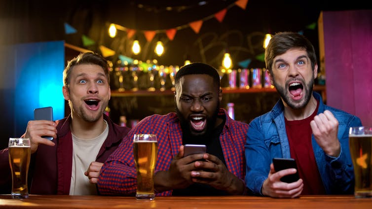 Three sports fans sit at a sports bar with beer, watching the game and looking at their cellphones