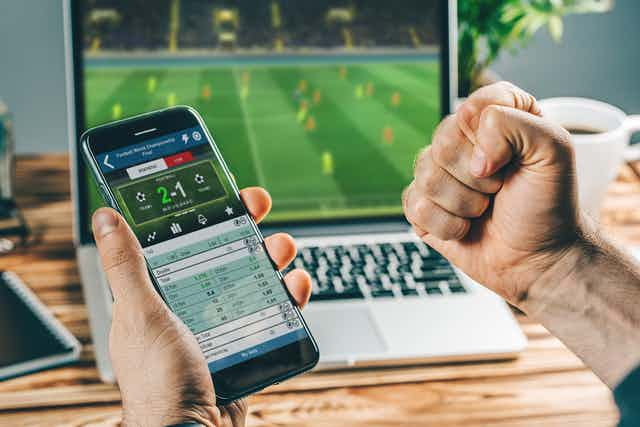 Man sits with his phone in front of a computer, a betting app is open as a soccer match plays in the background