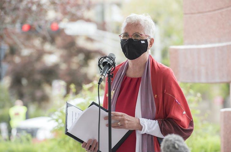 Brenda Murphy se tient debout devant un lutrin
