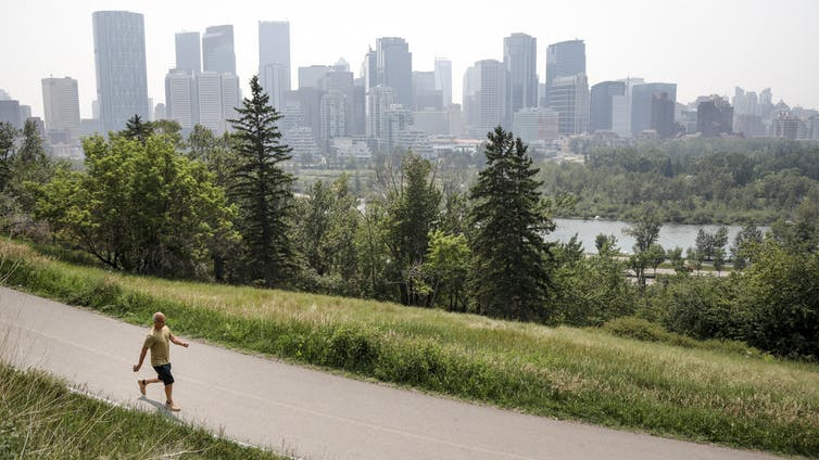 A man walking on a park path with the Calgary skyline in the distance, with a haze of smoke