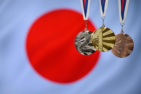 Les trois médailles olympiques placées en premier plan du drapeau du Japon