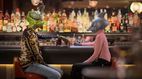 A grasshopper/human and a dolphin/human sit at a bar