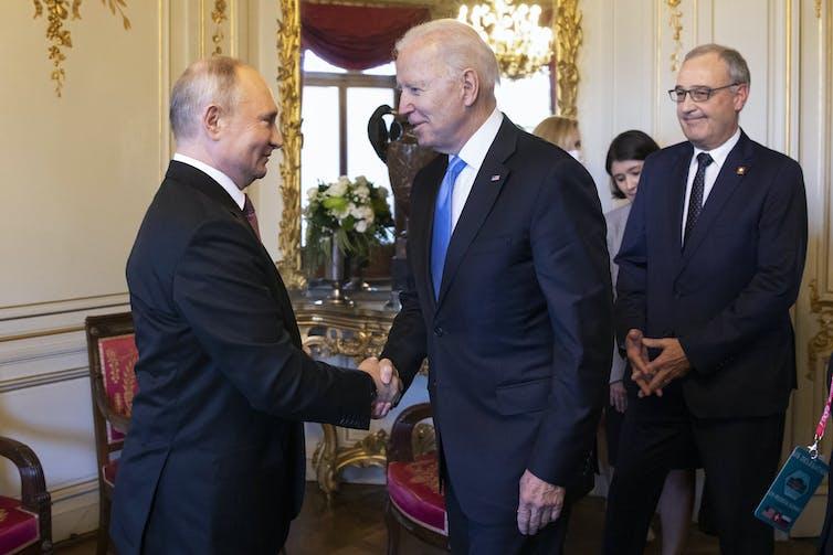Vladimir Putin shaking hands with Joe Biden