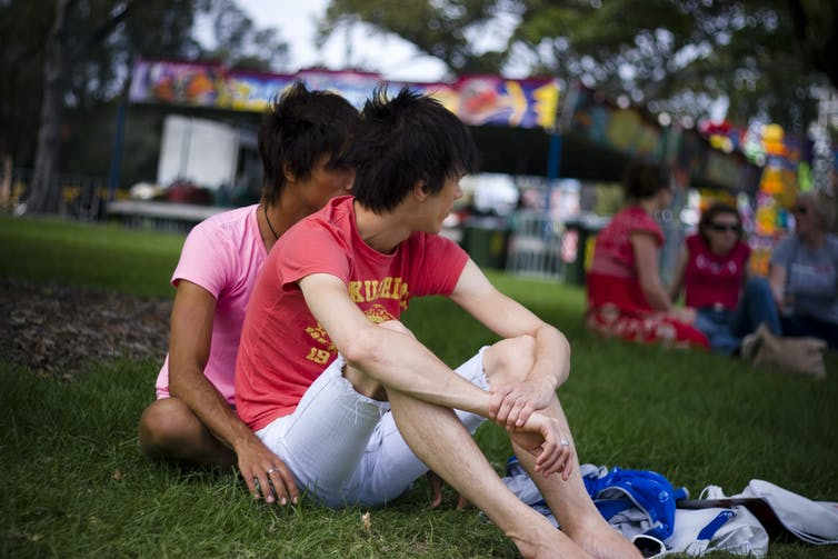 A gay couple sitting on a lawn.