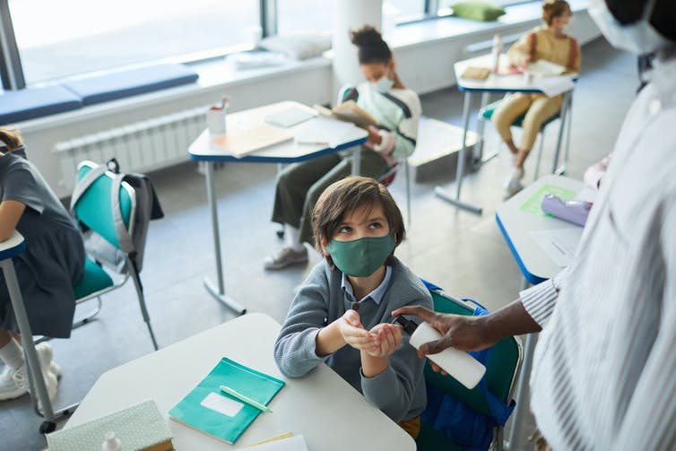 School student wearing mask holds out hands for hand sanitiser offered by masked teacher