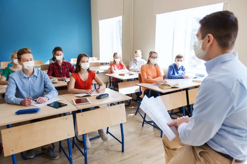 Masked students in classroom listening to masked teacher