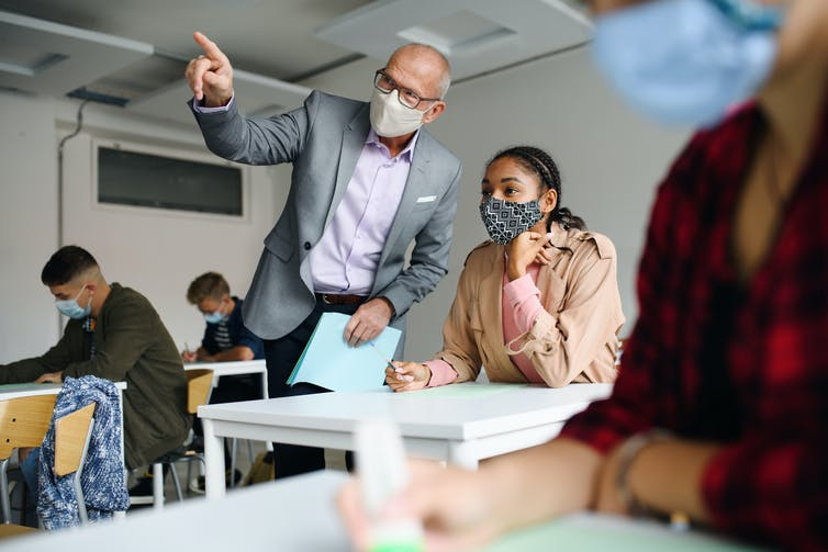 Masked teacher explains a point to masked student