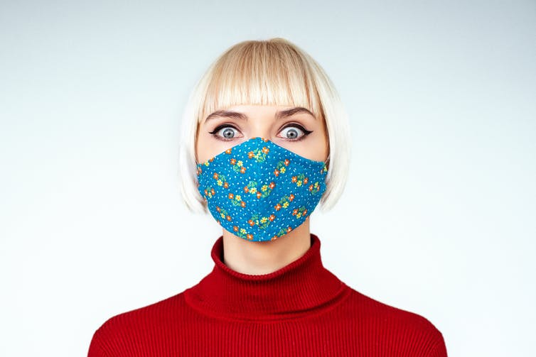 Women wearing a mask with wide-eyed expression