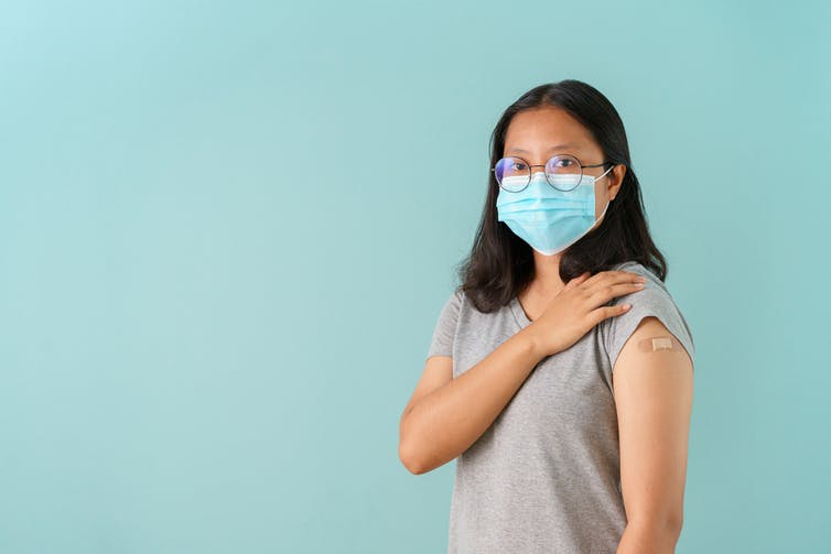 Teenager wearing face mask showing bandaid on shoulder just vaccinated