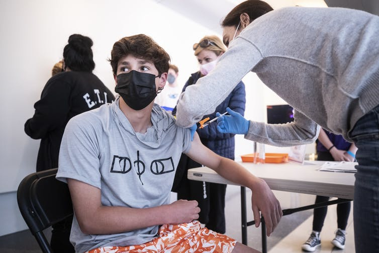 A 14 year old receiving a COVID-19 vaccine in California, USA