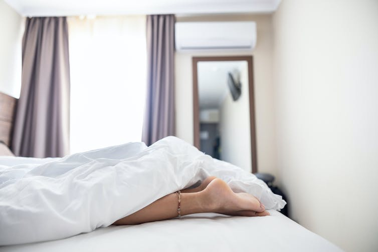Woman's feet stick out of the end of a bed.