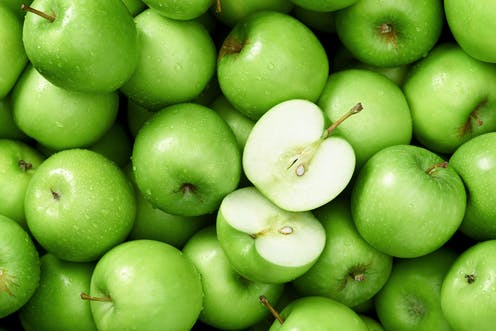 Green apples with one cut open.
