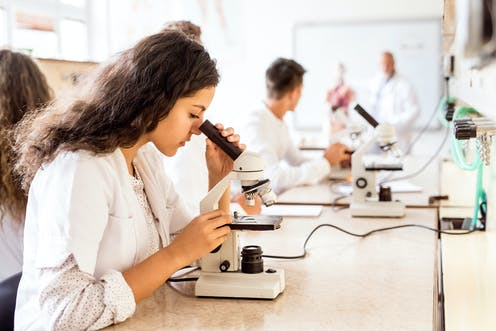 Senior students in lab coats looking through microscopes.