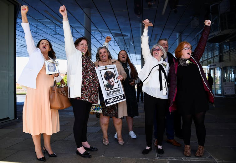 A group of seven people looking joyous with their fists in the air. One holds a sign with a photo of her family member and the word 'innocent'.