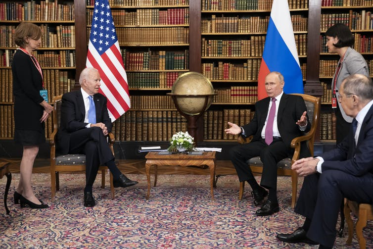 US president Joe Biden and Russian president Vladimir Putin surrounded by aides at a summit meeting in Geneva in June 2021.