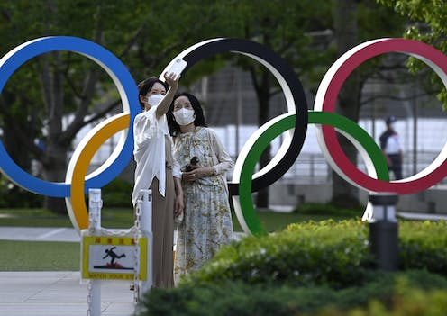 Two visitors pose for selfie next to Olympic rings.