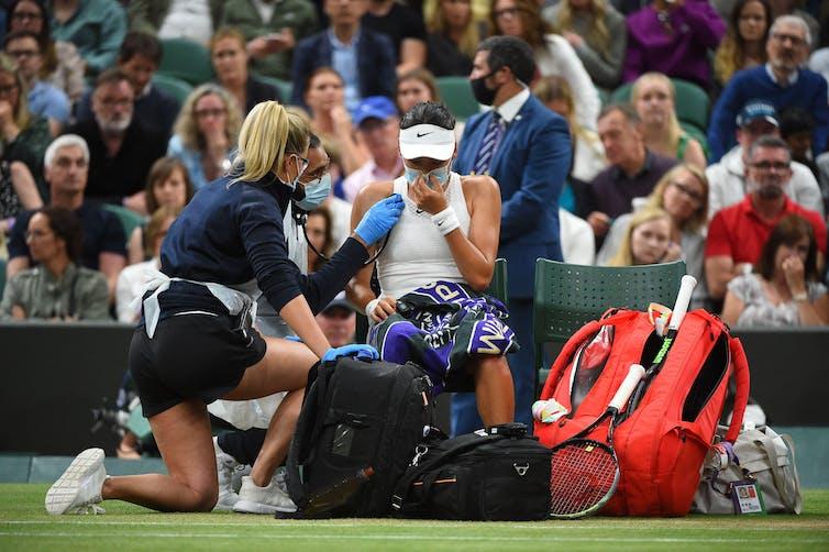 Healthcare professionals attend to tennis player Emma Raducanu during a Wimbledon match