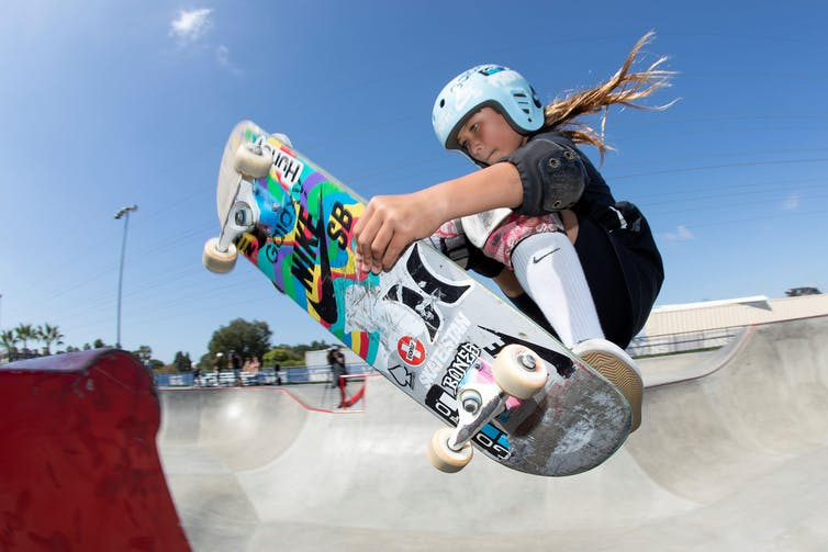A young girl in a helmet, black sports clothes and white socks and trainers does a jump on her skateboard