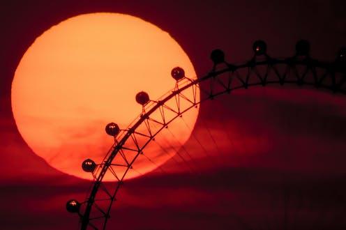 The sun sets behind the London Eye.