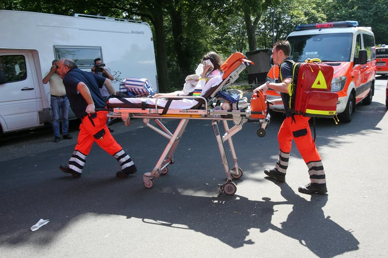 Paramedics lead a patient to an ambulance on a stretcher.