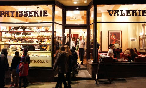 Patisserie Valerie shopfront with customers in the evening