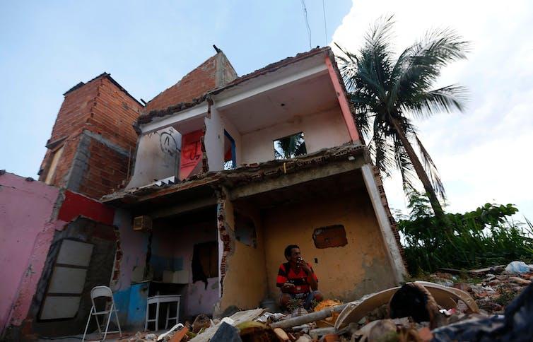 Luis Geraldo, 52 ans, fume une cigarette dans les décombres de sa maison après qu'une grande partie de la favela Vila Autodromo a été démolie pour faire place au parc olympique de Rio 2016