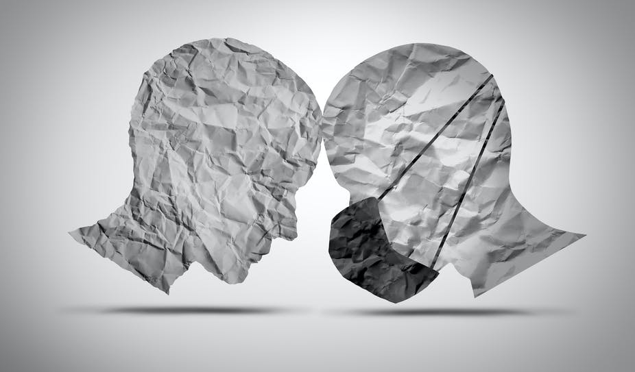 Two paper cut outs of human heads - one wearing a mask, one not.