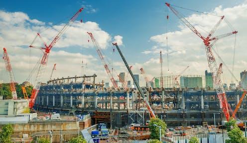 Cranes tower over a partially built stadium