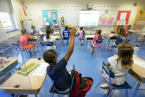 Children in a classroom; one is raising his hand.