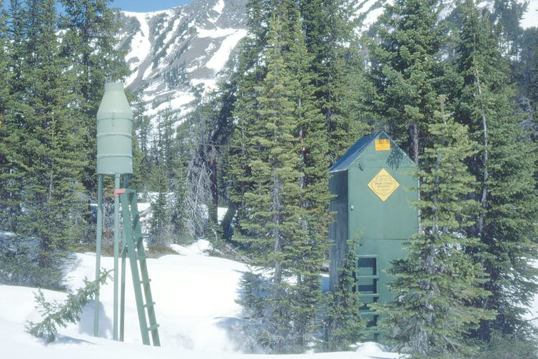 A small green metal tower and green wooden box in a snowy mountain forest.