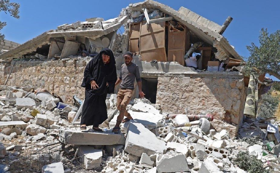 Deux habitants marchent sur les décombres d'une maison, après un bombardement des troupes du régime, à Serja dans la province d'Idlib, le 17 juillet dernier.