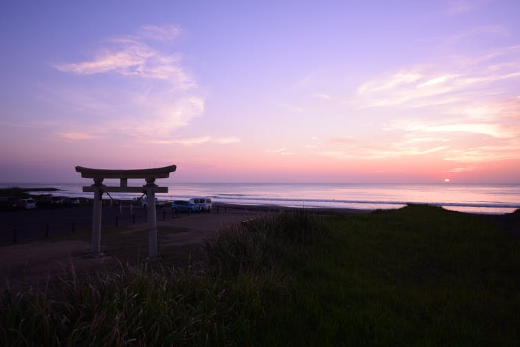 A sunrise over a beach with a Japanese arch in the foreground.