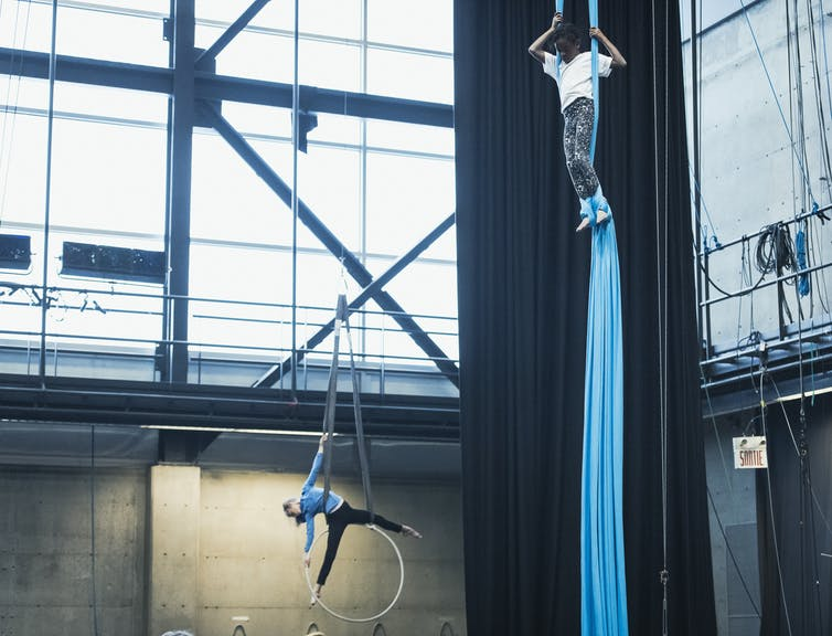 Two children performing aerial circus arts: on climbing a blue rope and one on a suspended hoop