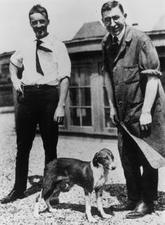 two men in early 20th C clothes standing with a dog between them