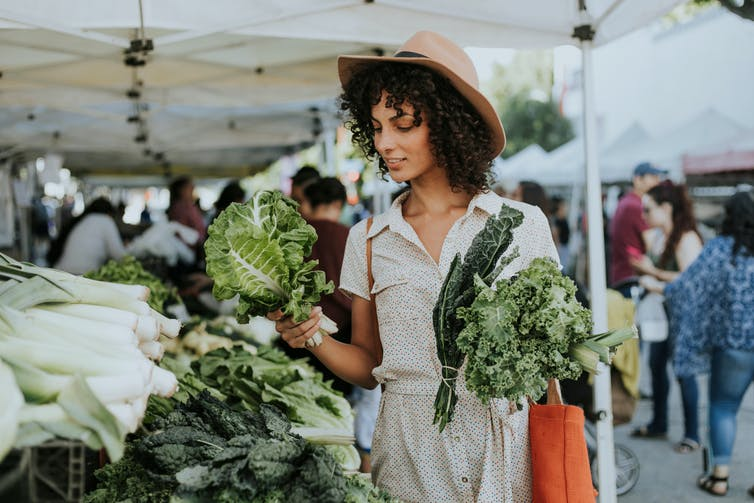 Woman buying kale at the market.
