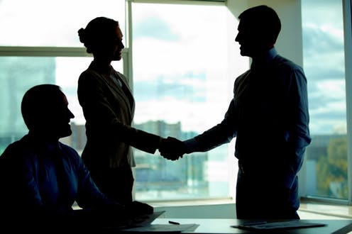 Business people in silhouette shaking hands on a deal