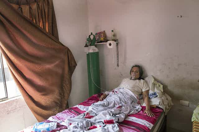 Woman with COVID-19 using oxygen tank in her home in Lima, Peru