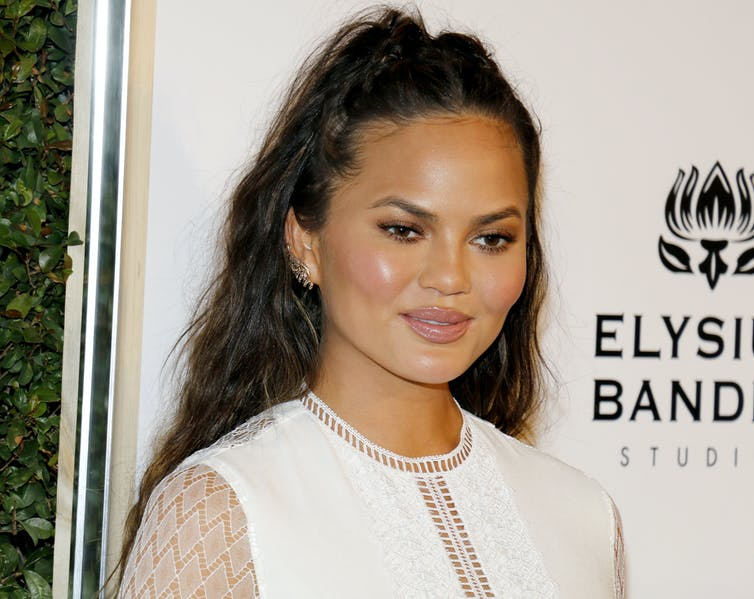 Chrissy Teigen in a white dress with her hair pulled back