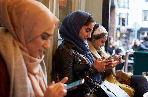 Three women wearing hijabs sitting side by side outside a shop and texting