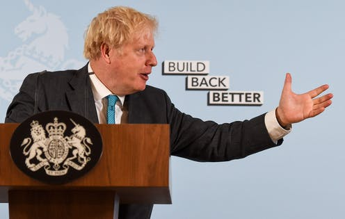 """Boris Johnson gestures while speaking at a podium, with a background reading """"Build Back Better."""" His arm is extended towards the text."""
