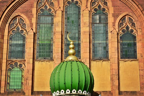 The top of a mosque with the crescent moon sitting in front of a Christian church in the UK.