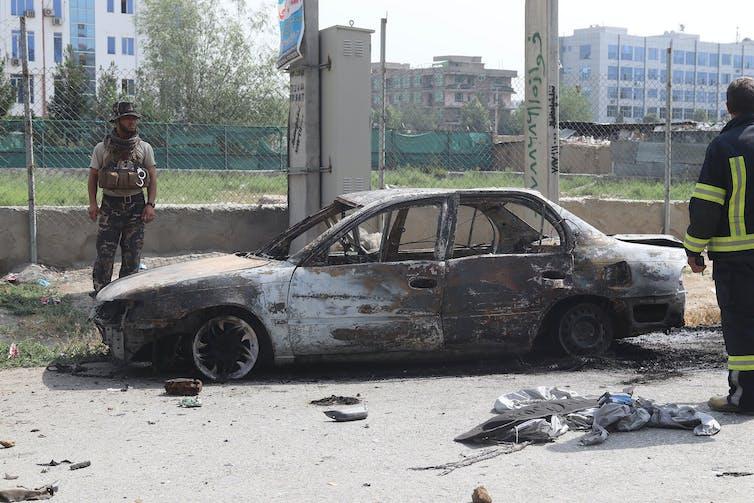 Des agents de sécurité afghans inspectent un véhicule endommagé.