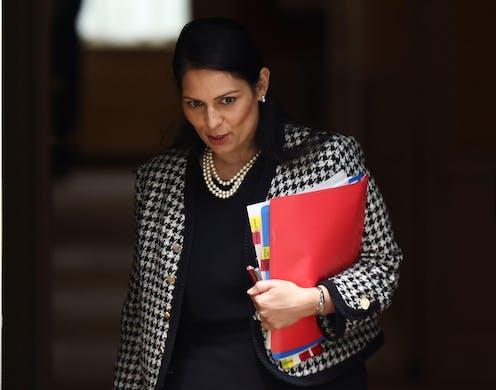 Home secretary Priti Patel carrying folders under her arm.