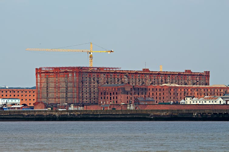Cranes and scaffolding surround a large red-brick warehouse seen from across the water