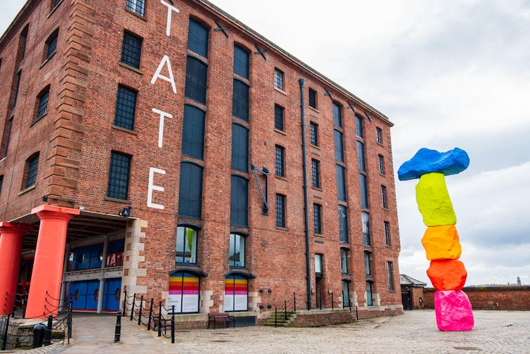 Exterior of Tate Liverpool art gallery in the Albert Dock Area in Liverpool, Merseyside with a colourful outdoor sculpture